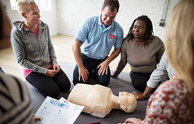 Group of people gathered around a CPR manequin